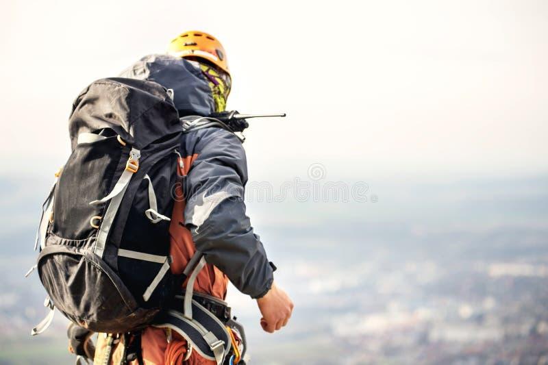 Nahaufnahme eines Bergsteigers von der Rückseite im Gang und mit einem Rucksack mit Ausrüstung auf dem Gurt, Stände auf einem Fel lizenzfreie stockfotografie