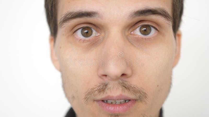 Nahaufnahme eines ?berraschten emotionalen Mannes mit den braunen Augen, die die Kamera untersuchen lizenzfreies stockfoto