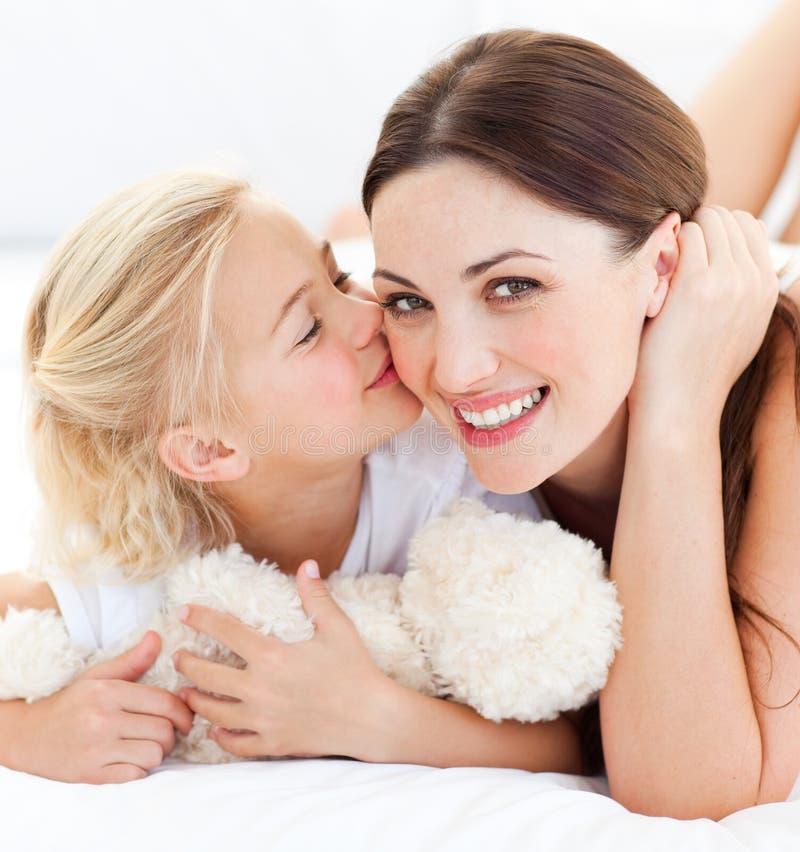 Nahaufnahme eines blonden kleinen Mädchens, das ihre Mutter küßt lizenzfreies stockfoto