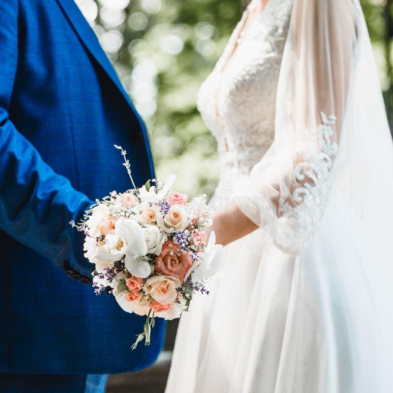 Nahaufnahme eines Braut ` s Blumenstraußes in den Händen eines liebevollen Paares stockbilder