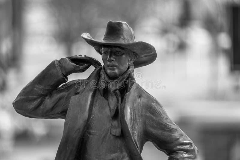 Nahaufnahme eines Bronzecowboys auf einem undeutlichen Hintergrund stockfotografie