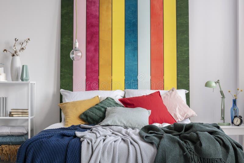Nahaufnahme eines bunten Betts mit den Kissen und Decken, die gegen weiße Wand mit gestreifter Malerei im Schlafzimmerinnenraum s lizenzfreie stockfotografie