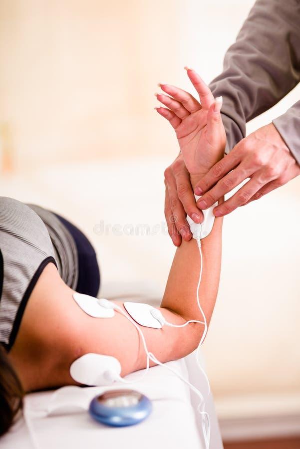 Nahaufnahme eines deportist, welches mit einer Hand die elektrische Maschine hält und die electrostimulator Elektroden der Arm se lizenzfreie stockfotografie
