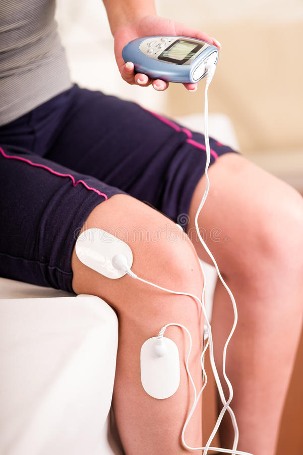 Nahaufnahme eines deportist, welches mit einer Hand die elektrische Maschine und die electrostimulator Elektroden in ihrem Bein h stockfotos