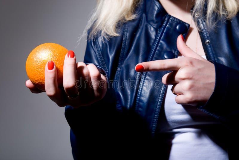 Nahaufnahme eines Fingers, der auf eine Orange zeigt stockfotografie