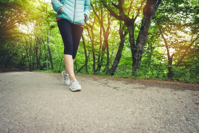 Nahaufnahme eines Fußes eines sportlichen Mädchens in den Gamaschen und in den Turnschuhen, bevor im Wald das Konzept Sports des  stockfotografie