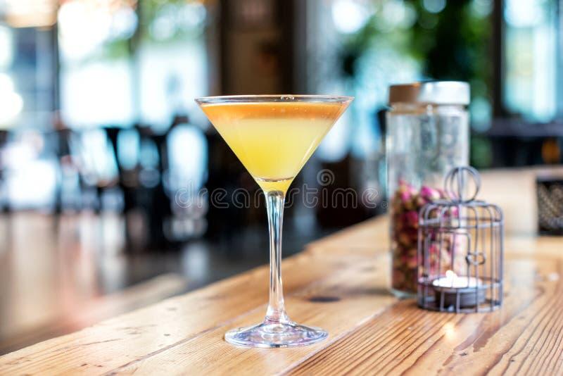 Nahaufnahme eines gelben Cocktails in einem aufgehaltenen Glas stockbilder