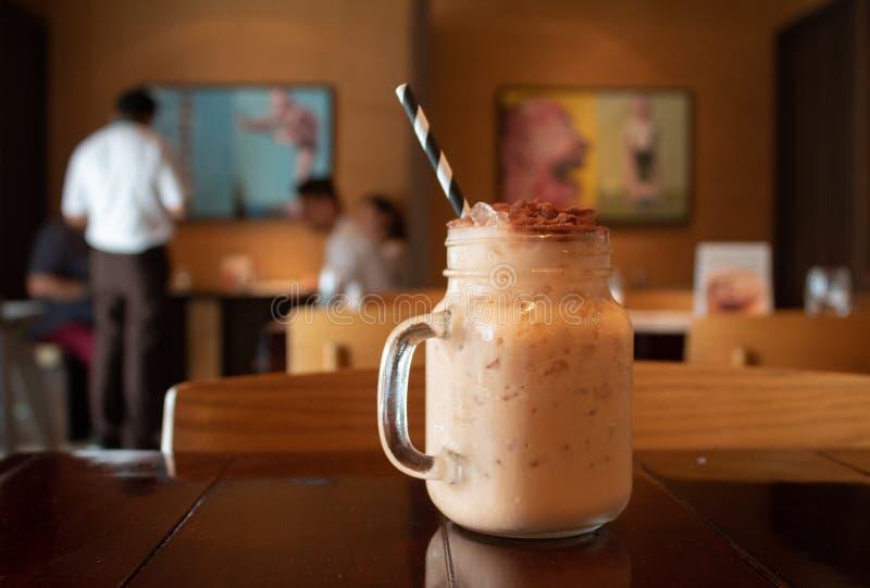 Nahaufnahme eines geschmackvollen thailändischen Milchtees auf einer Tabelle in einem Café mit einem unscharfen Hintergrund lizenzfreie stockfotos