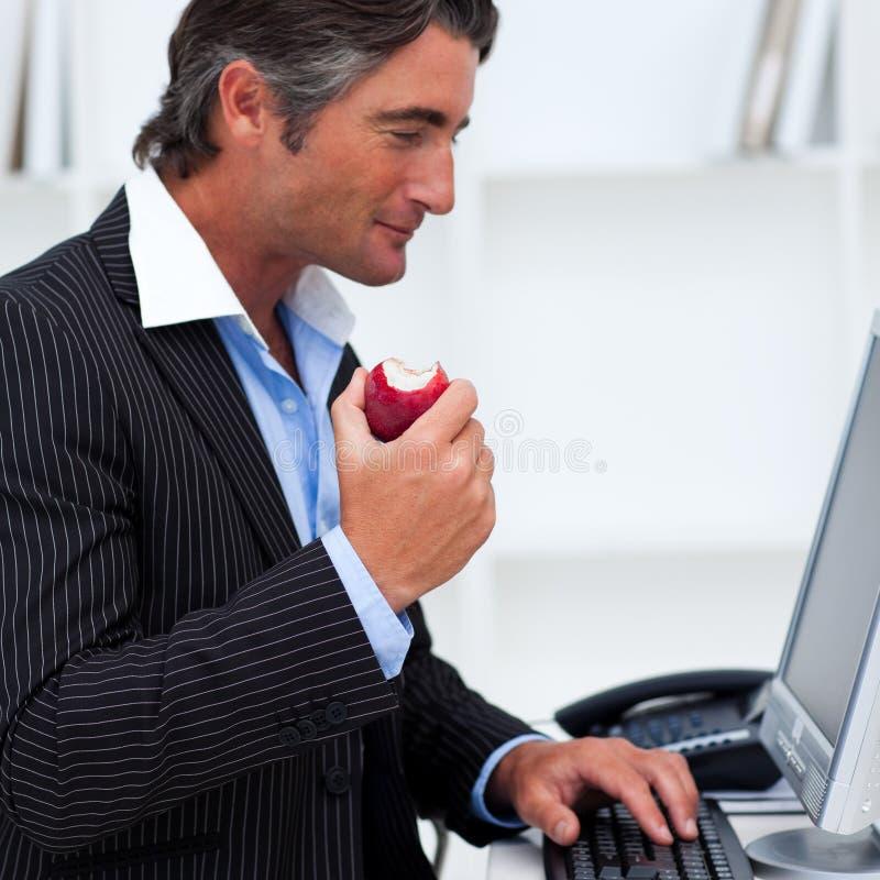 Nahaufnahme eines glücklichen Geschäftsmannes, der einen roten Apfel isst lizenzfreies stockfoto
