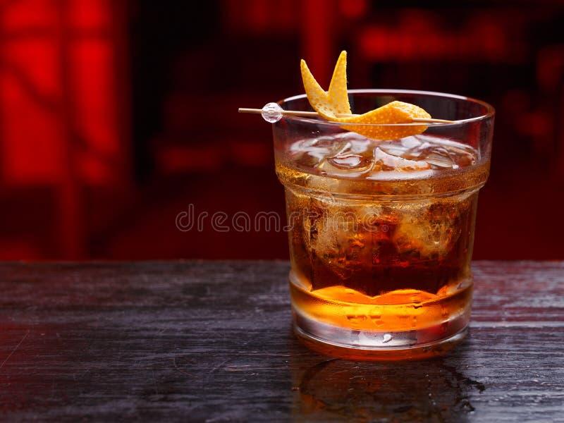 Nahaufnahme eines Gottvatercocktails im kurzen Glas, Gin, stehend auf dem Barzähler, lokalisiert auf einem roten hellen Hintergru lizenzfreie stockfotografie