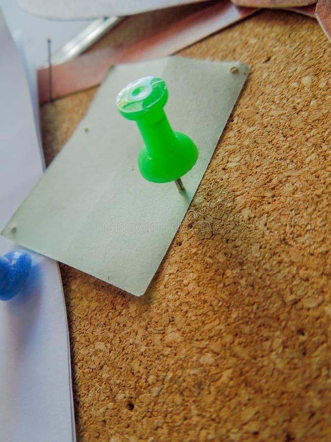 Nahaufnahme eines grünen Stiftes, der ein Papier mit einer Korkenauflage darunterliegend feststeckt stockfotos