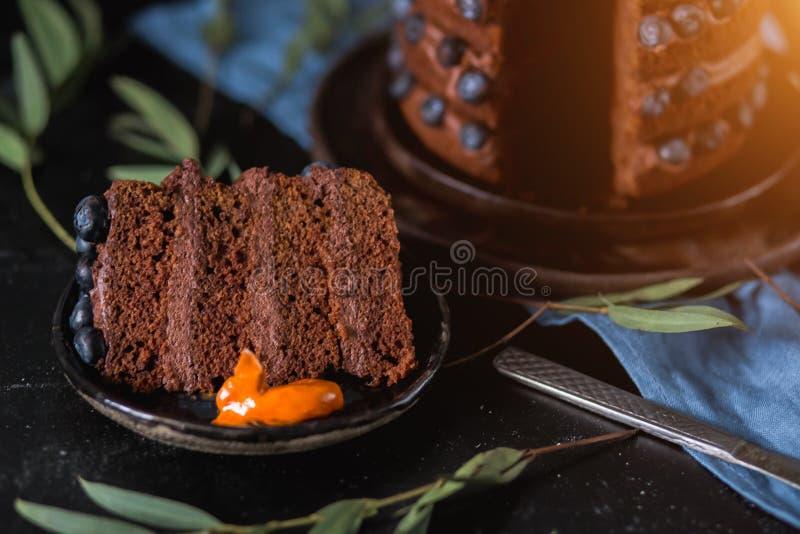 Nahaufnahme eines großen Stückes des köstlichen Schokoladenkuchens mit Beeren auf einem schwarzen Hintergrund lizenzfreie stockfotografie