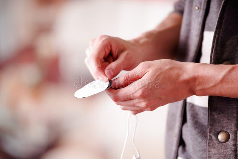 Nahaufnahme eines Handmannes, der ein Band der electrostimulator Elektroden in einem unscharfen Hintergrund herausnimmt lizenzfreie stockbilder
