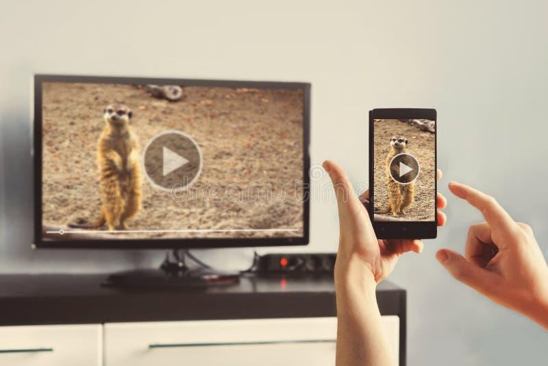 Nahaufnahme eines intelligenten Telefons wird an ein intelligentes Fernsehen angeschlossen stockbild