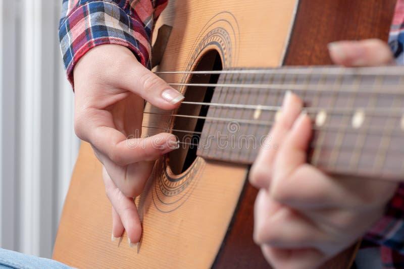 Nahaufnahme eines junge Frau ` s übergibt das Spielen der Gitarre stockbild