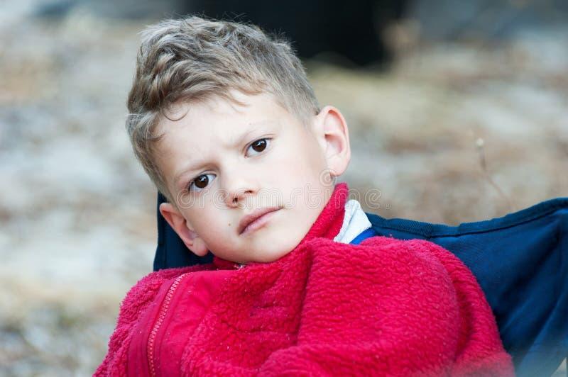Nahaufnahme eines Jungen in einem roten Vlies auf einem blauen Stuhl stockfotografie