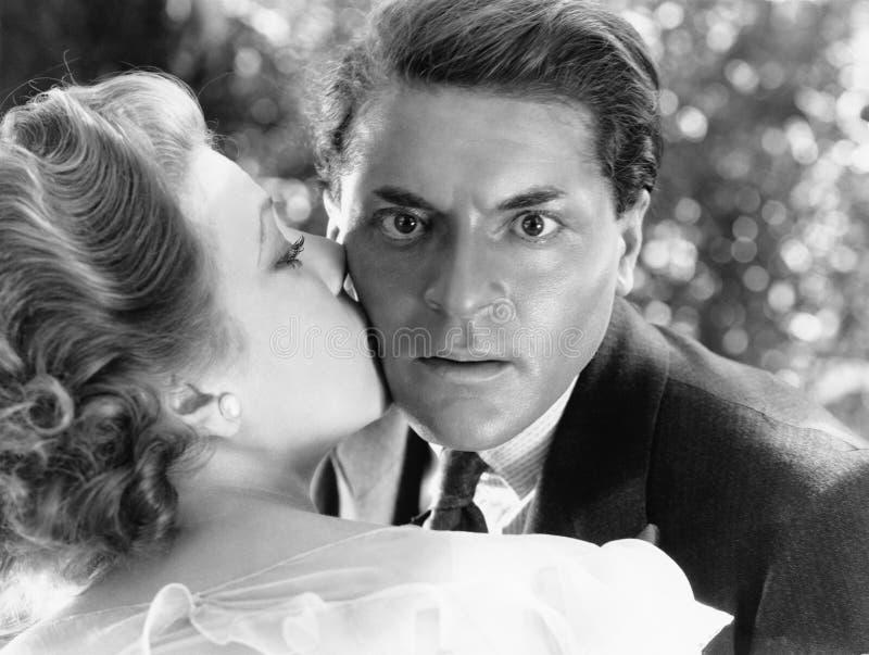 Nahaufnahme eines jungen Mannes, der von einer jungen Frau geküsst wird und schauend überrascht (alle dargestellten Personen sind lizenzfreies stockbild