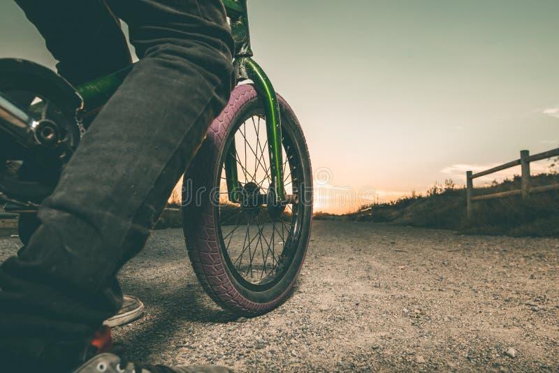 Nahaufnahme eines Kerls mit einem Fahrrad in einem Sonnenuntergang stockfotos
