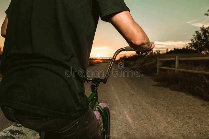Nahaufnahme eines Kerls mit einem Fahrrad in einem Sonnenuntergang stockbilder