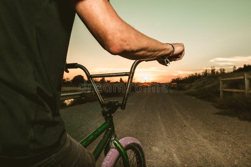 Nahaufnahme eines Kerls mit einem Fahrrad in einem Sonnenuntergang lizenzfreies stockfoto