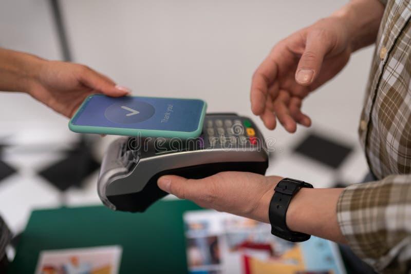 Nahaufnahme eines Kunden, der eine erfolgreiche Zahlung über PayPass tut lizenzfreie stockfotos