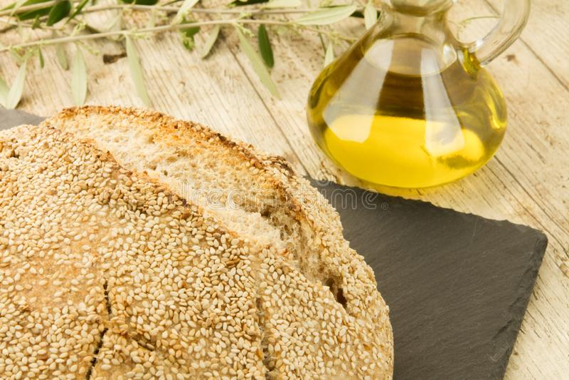 Nahaufnahme eines Laibs des selbst gemachten Brotes mit Samen des indischen Sesams, Ampulle des reinen Extraoliven?ls und einem ? stockfoto