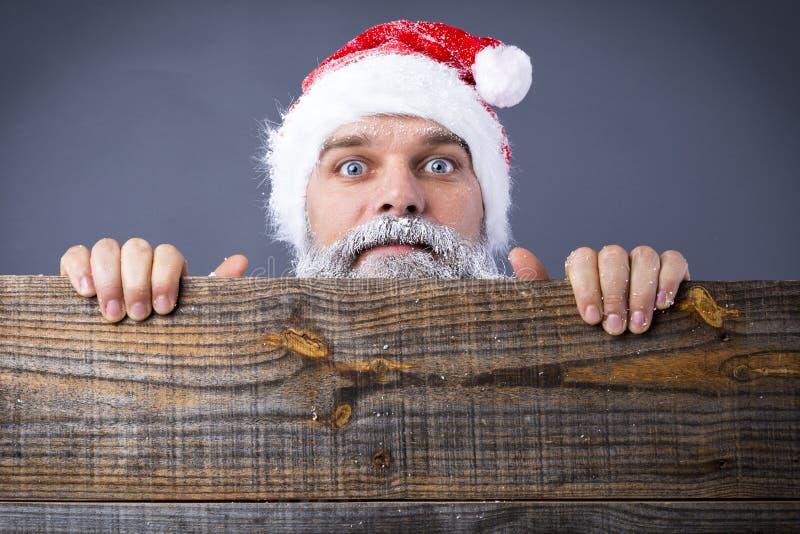 Nahaufnahme eines lustigen Mannes mit dem gefrorenen Bart, der Sankt-Rotkappe trägt stockbilder