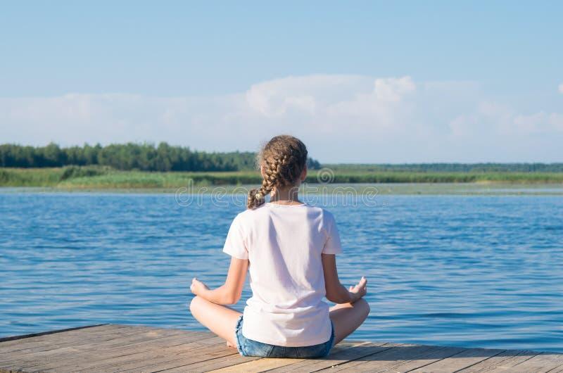 Nahaufnahme eines Mädchens, auf dem Pier, Praxisyoga, hintere Ansicht, gegen den Hintergrund einer schönen Landschaft stockbilder