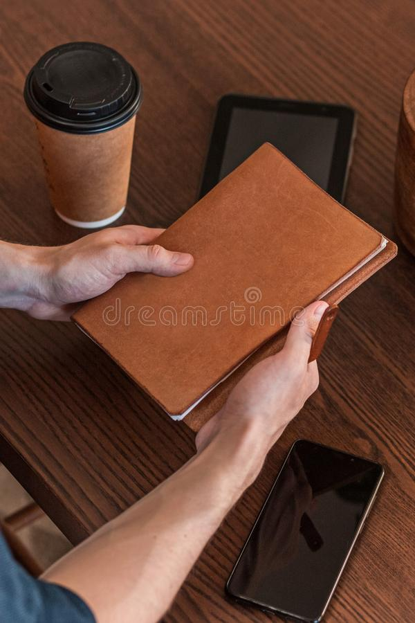 Nahaufnahme eines Mannes, der an einem Schreibtisch in einem Büro arbeitet und Notizbuch mit copyspace hält stockfotografie