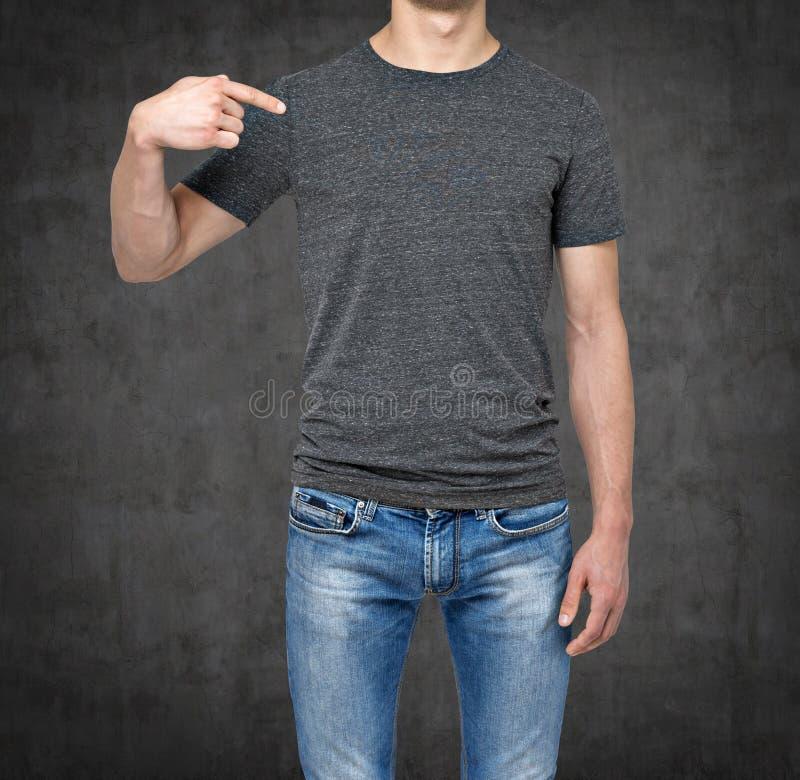 Nahaufnahme eines Mannes, der seinen Finger auf einem leeren grauen T-Shirt zeigt lizenzfreies stockbild