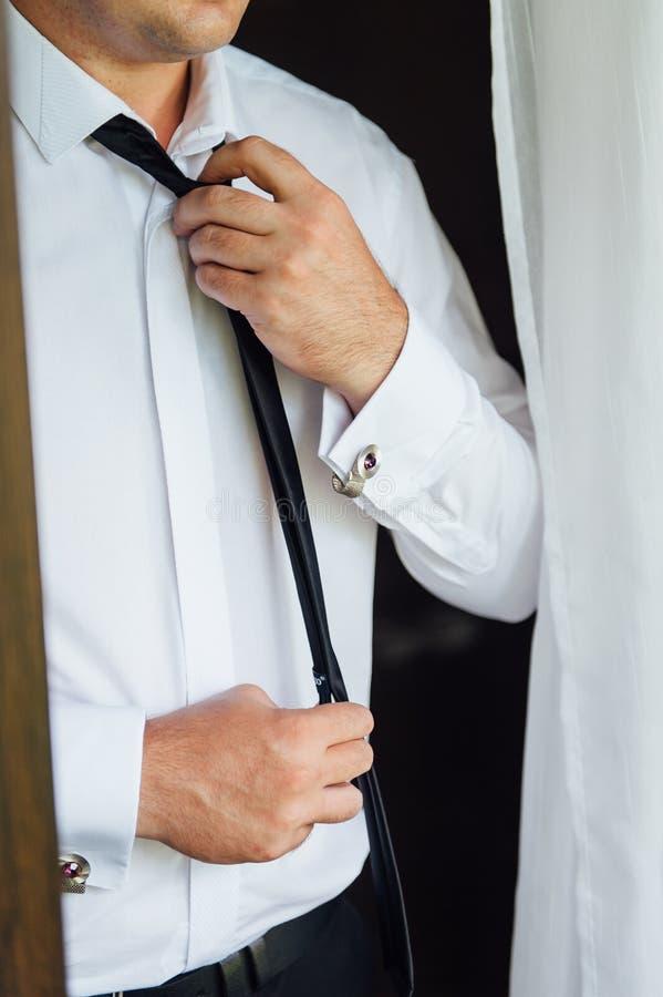 Nahaufnahme eines Mannes in einem Smoking, der seinen Weinlesemanschettenknopf repariert Bräutigamfliegenmanschettenknöpfe lizenzfreie stockfotografie