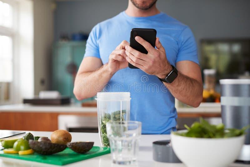 Nahaufnahme eines Menschen mit Fitness-Tracker, um die Kalorien für Post-Workout-Juice-Drink zu zählen, macht er gerade ein Fitne stockfotos