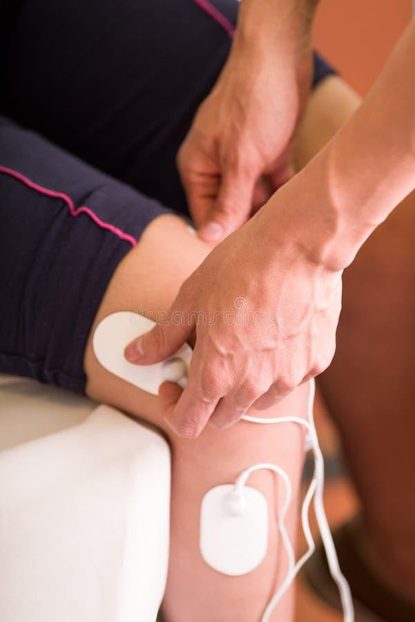 Nahaufnahme eines persönlichen Trainers, der an die electrostimulator Elektroden in das Bein eines weiblichen deportist, umgedreh lizenzfreie stockfotografie