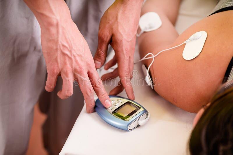 Nahaufnahme eines persönlichen Trainers, der mit einer Hand die elektrische Maschine mit den electrostimulator Elektroden in berü lizenzfreies stockbild