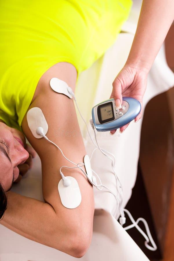 Nahaufnahme eines persönlichen Trainers, der mit einer Hand die elektrische Maschine mit den electrostimulator Elektroden in hält lizenzfreies stockbild