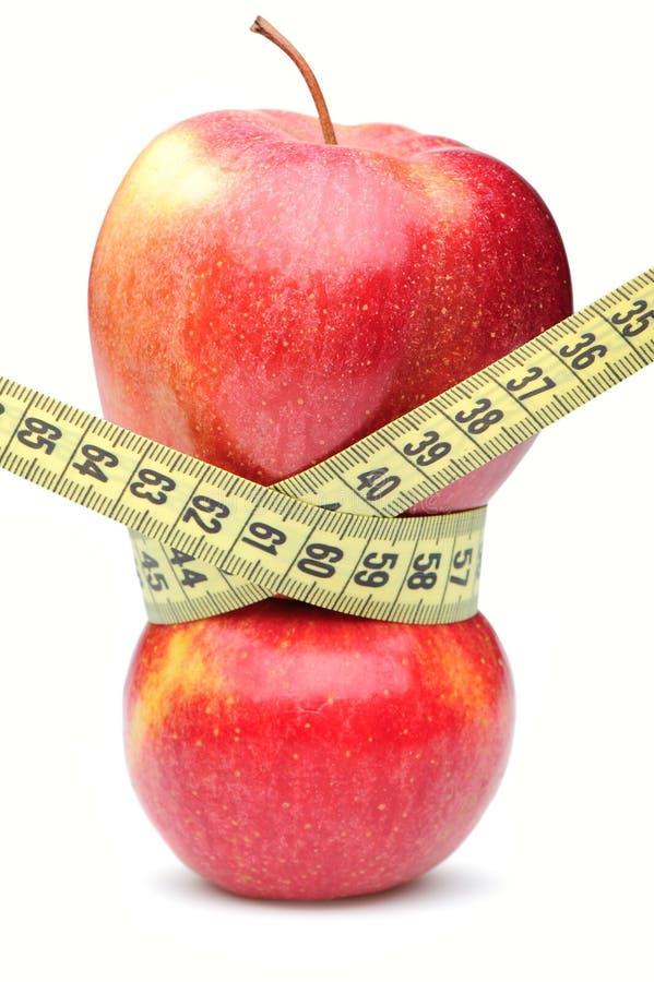 Nahaufnahme eines roten Apfels mit einem messenden Band lizenzfreie stockfotografie