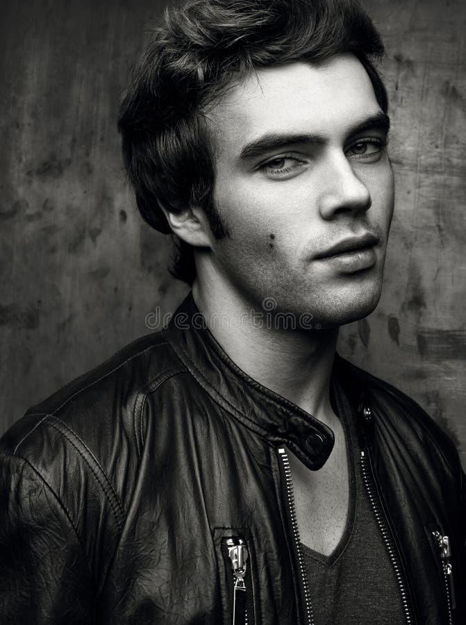 Nahaufnahme eines schönen jungen Mannes in der schwarzen Lederjacke Kontrastschwarzes stockbild