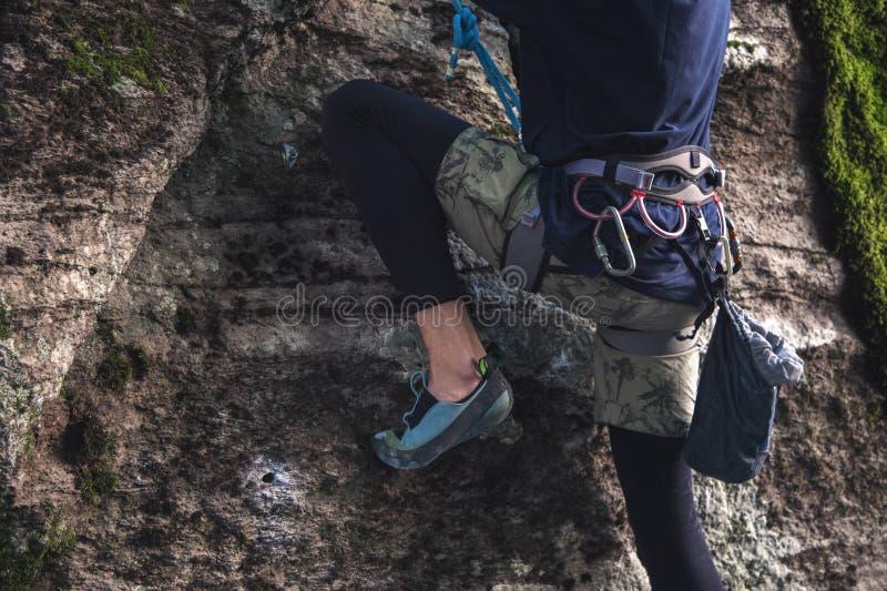 Nahaufnahme eines Schenkelbergsteigers mit Ausrüstung auf einem Gurt, Stände auf einem Felsen lizenzfreie stockfotos