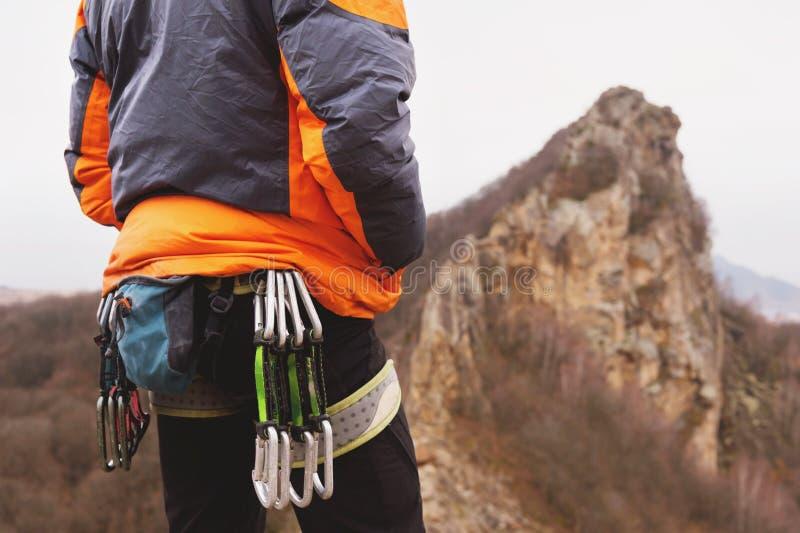 Nahaufnahme eines Schenkelbergsteigers mit Ausrüstung auf einem Gurt, Stände auf einem Felsen stockbilder