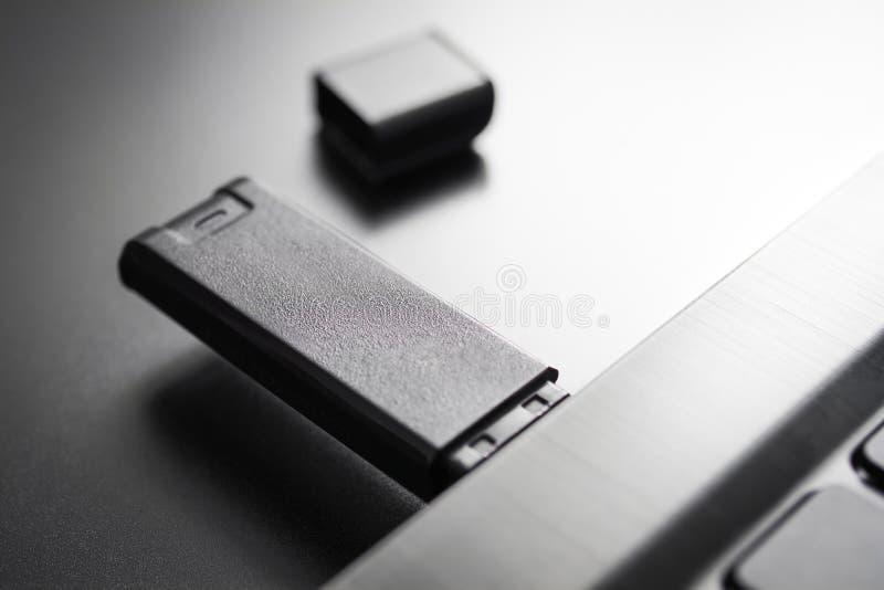 Nahaufnahme eines Schwarzes USB-Memorysticks verstopft in den USB-Port eines schwarzen Notizbuches, Seitenansicht stockfotos