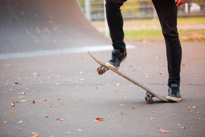 Nahaufnahme eines Skateboardfahrer ` s Fußes in einem Herbstrochenpark stockfotos