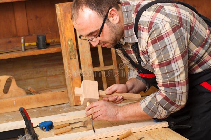 Nahaufnahme eines Tischlers, der mit einem Meißel arbeitet und Werkzeuge schnitzt stockfotos