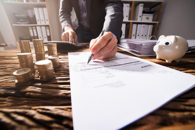 Nahaufnahme eines Wirtschaftler ` s Handunterzeichnenden Dokuments stockbilder