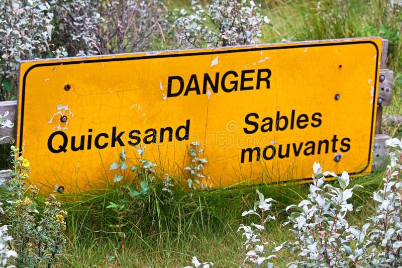 Nahaufnahme eines zweisprachigen Gefahrentreibsandzeichens lizenzfreies stockbild
