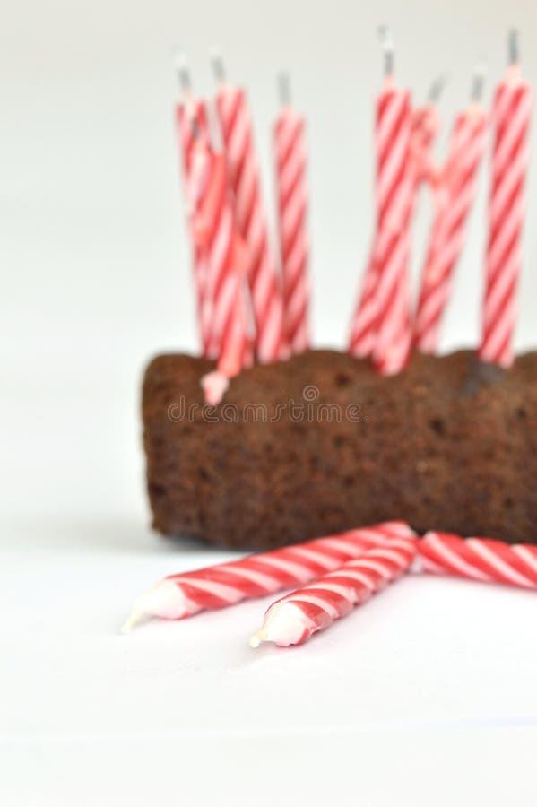 Nahaufnahme einiger Kerzen aus den Grund und einen Geburtstagskuchen im Hintergrund lizenzfreie stockbilder
