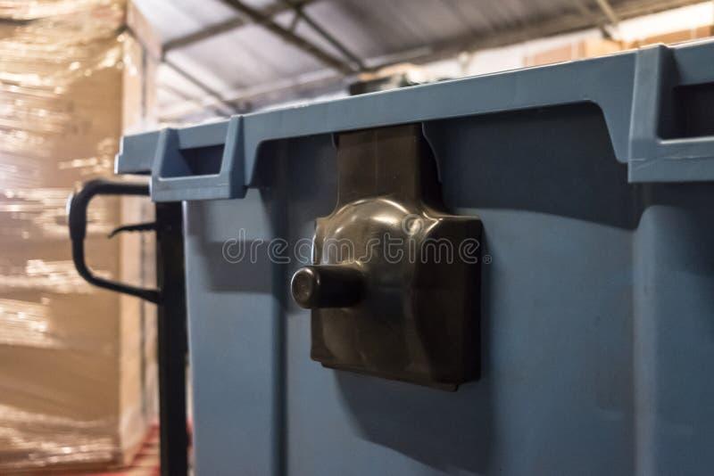 Nahaufnahme, flache Fokusansicht eines großen blauen Papierkorbes und Gabel pumpen den LKW, der in einer Lagermitte gesehen wird stockfoto