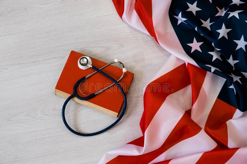 Nahaufnahme-Foto des Stethoskops und des roten Buches auf amerikanischer Flagge Medizin USA getrennte alte Bücher medizinischer G stockfotografie