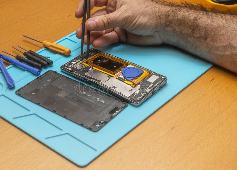 Nahaufnahme-Foto des Technikers Hand Repairing Cellphone lizenzfreies stockfoto