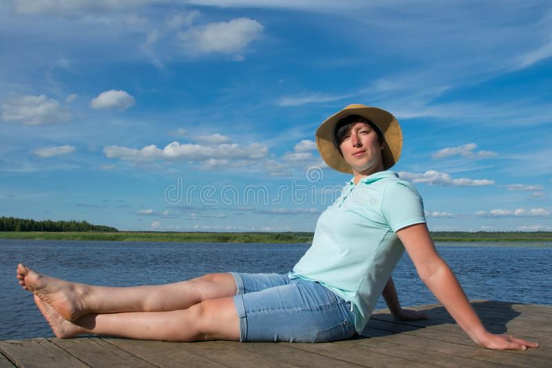 Nahaufnahme, Frau in einem Hut auf einem Pier, ist, genießend stillstehend und einen schönen Himmel und einen See lizenzfreie stockbilder