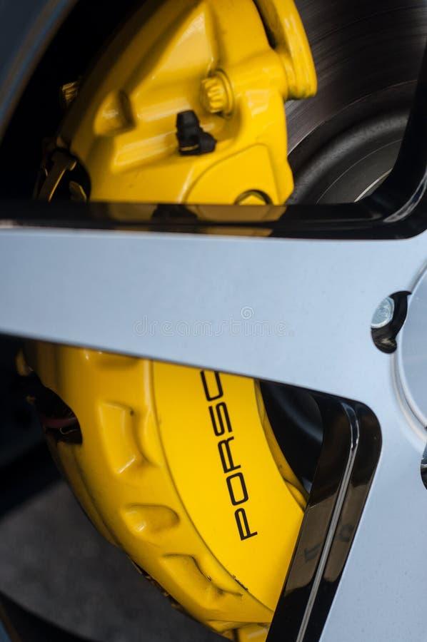 Nahaufnahme gelber Porsche-Bremse auf Porsche Cayenne lizenzfreie stockfotografie